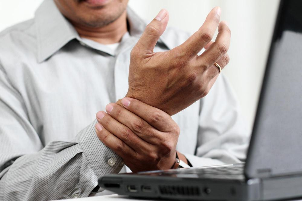 Man with wrist pain, at work who needs chiropractic care.